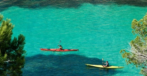 Kayakers paddling in clear blue-green waters